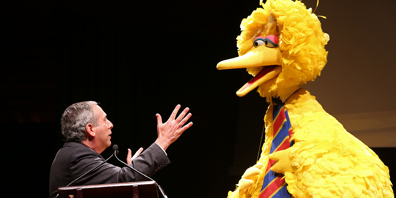 Harvard President Lawrence Bacow and Big Bird on stage