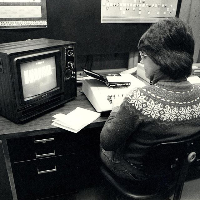 Black and white photo of woman on old computer