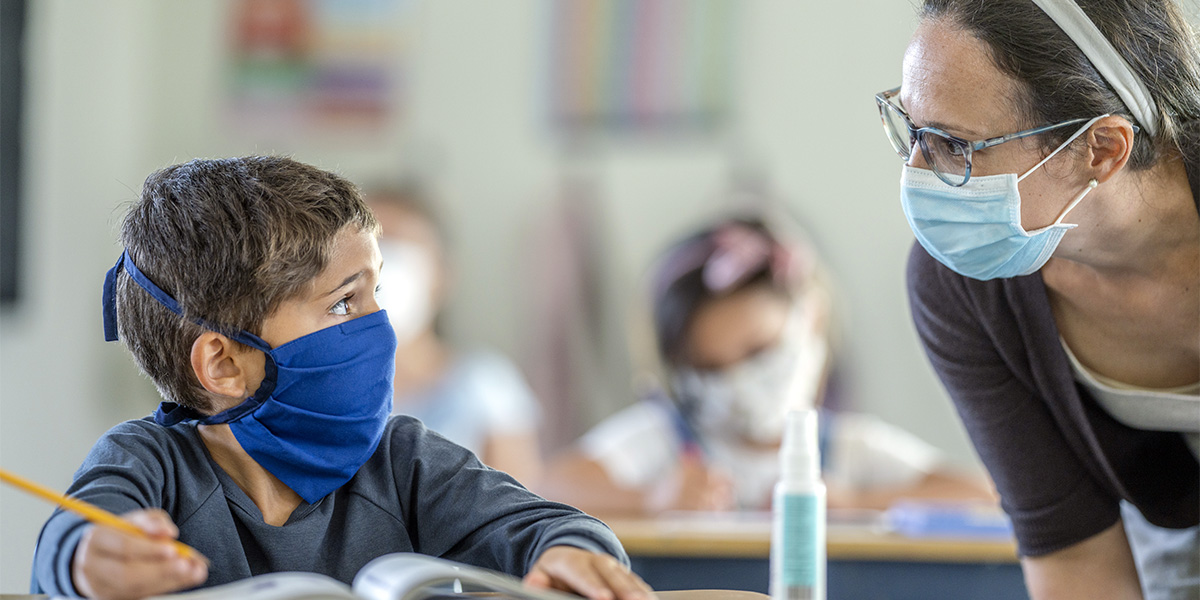 Child and teacher wearing masks in school