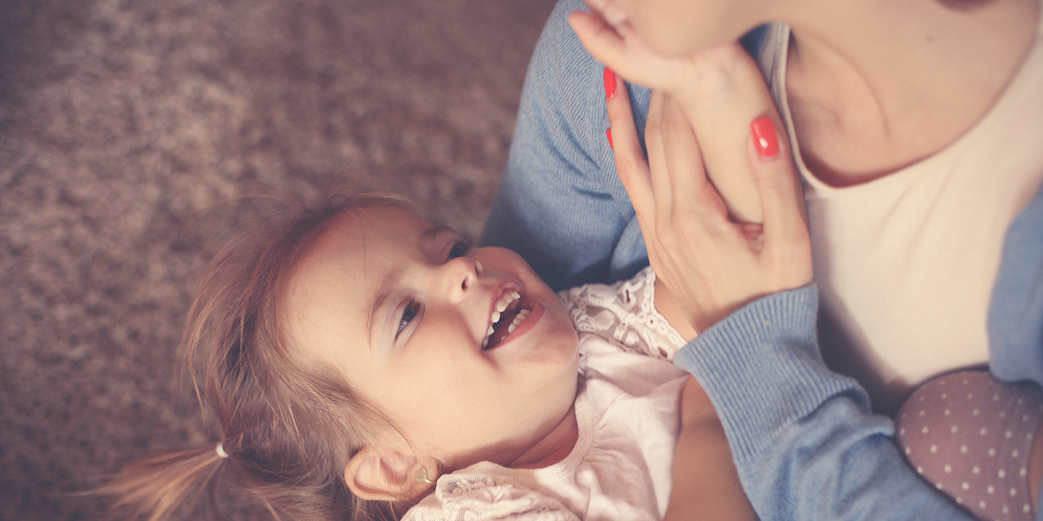 Young girl smiles up at her mother