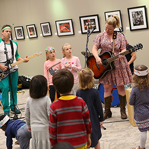 Musicians play guitars with children listening