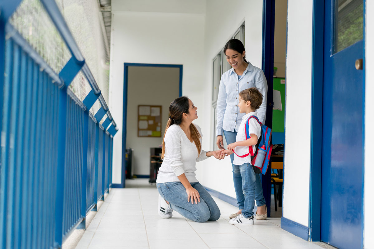 A photo of a mother kneeling next to her son and his teacher in a school hallway
