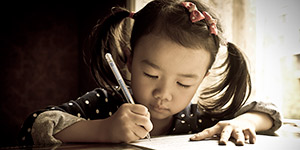 A young girl writes on a piece of paper