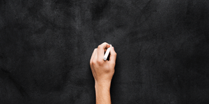 photo of a hand on a blackboard