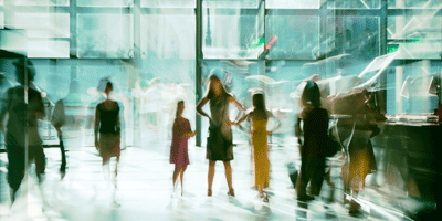 A blurry photograph of adults and children inside a museum