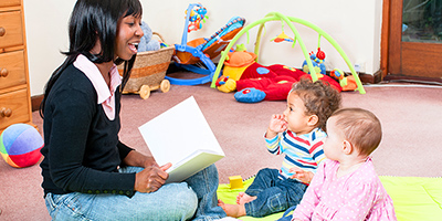Home daycare teacher reading to two infants