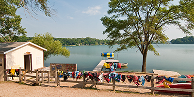Picture of a lake in summertime, with a camp house and a wooden fence hung with colorful lifejackets