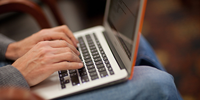 Close-up of hands over a laptop keyboard