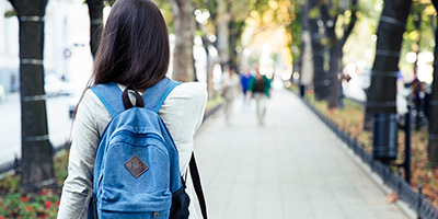 Female student from the rear, walking down long campus pathway