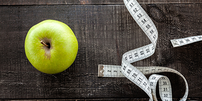photo of an apple and roll of measuring tape