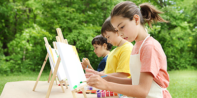 Three children painting on easels set up outside