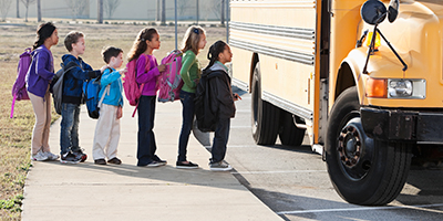 line of children getting onto a school bus