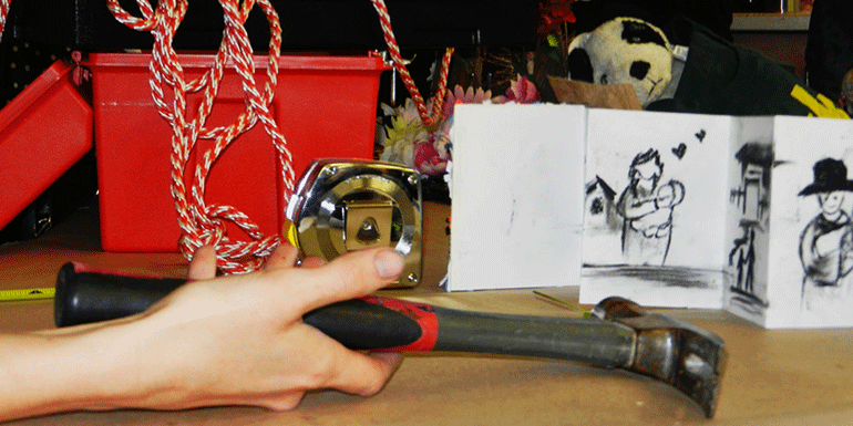 photo of hand with hammer and crafts in background