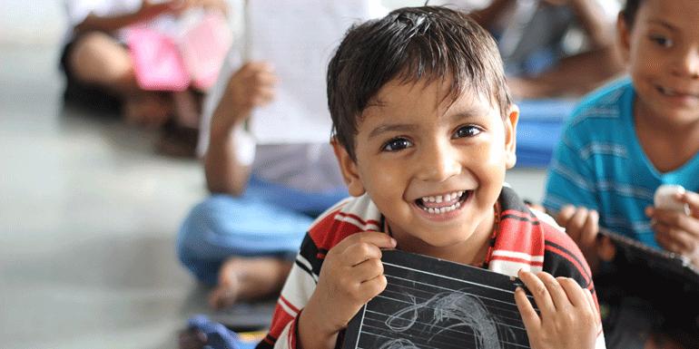a boy with a small chalkboard
