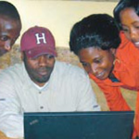 Haynes (baseball cap) demonstrates to teachers how to use one of the new computers at Crimson Academy in Rwanda