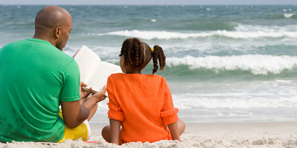 A father and daughter reading at the beach