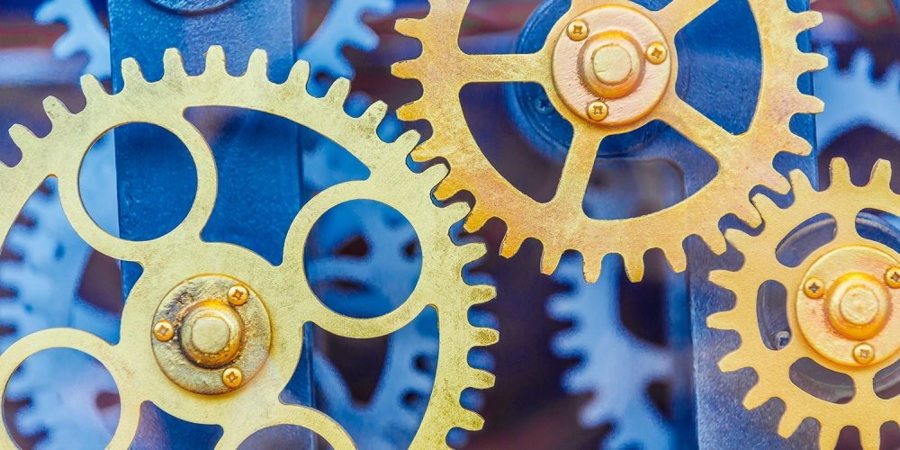 Gold-colored gears turning against a blue background various sizes