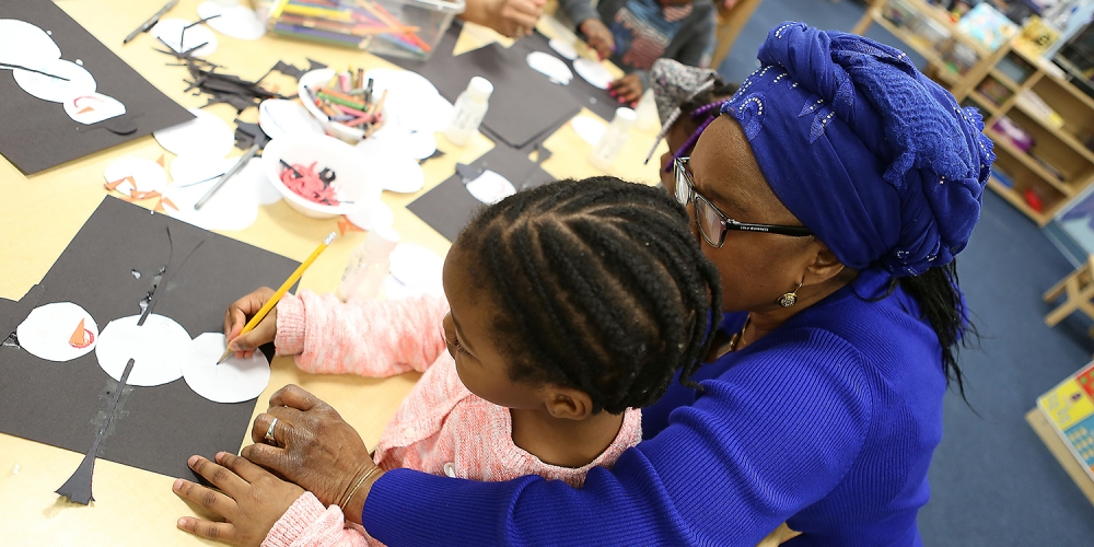 preschool teacher helping young girl with her drawing
