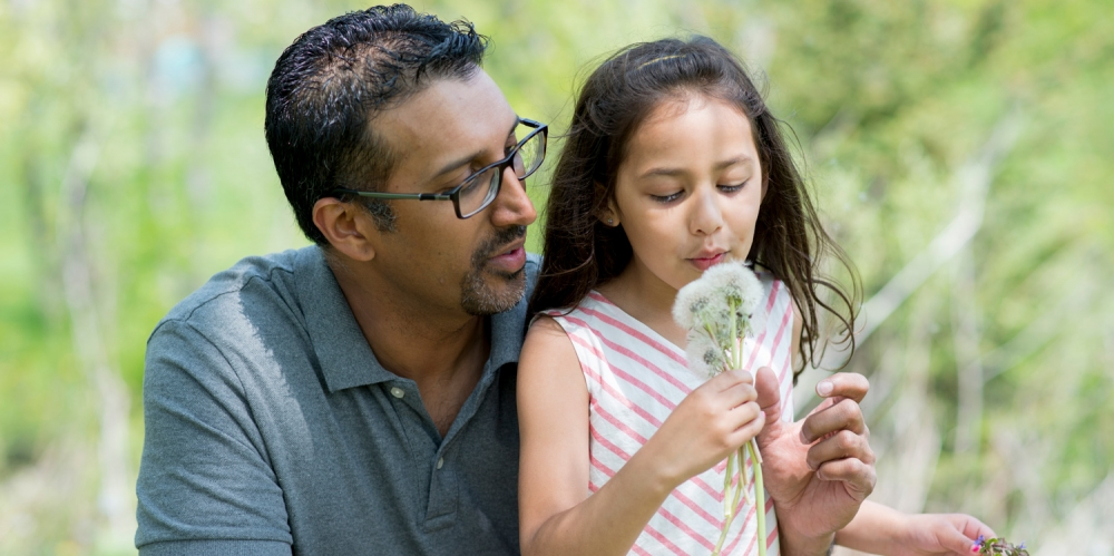 An image of a girl and her father blowing a dandelion