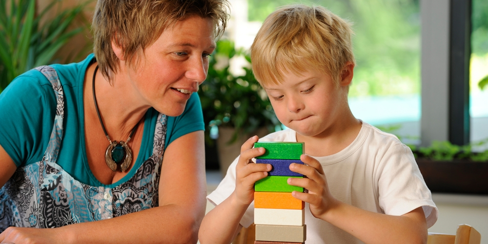 Teacher with a young child building a block tower