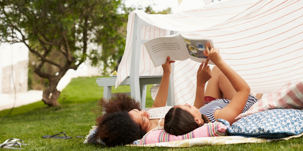 A mother and her daughter reading a book outside