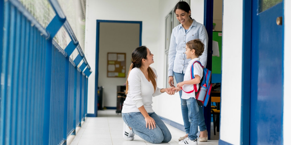 A photo of a mother kneeling next to her son and teacher in a school hallway