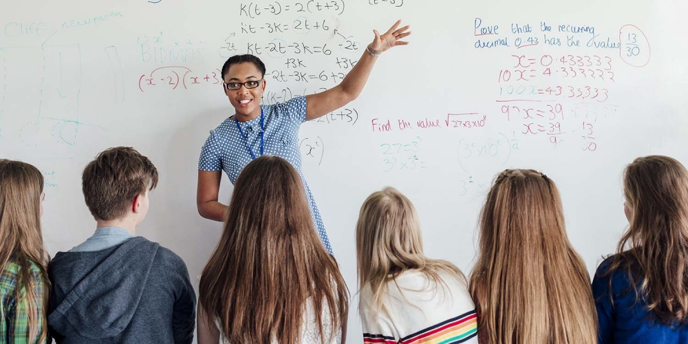 Math teacher in front of white board