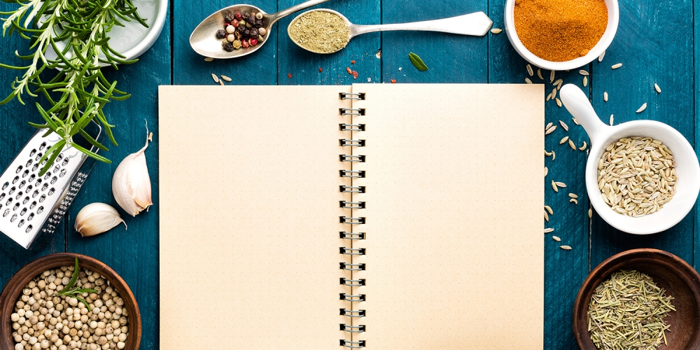 A blank page in an open notebook, surrounded by cooking ingredients