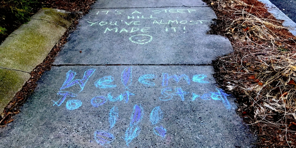 "sidewalk chalk message saying ""welcome to our street"""