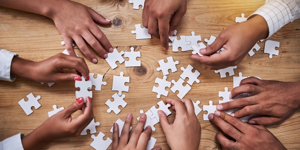 Seen from above, hands of a group of people putting together jigsaw puzzle