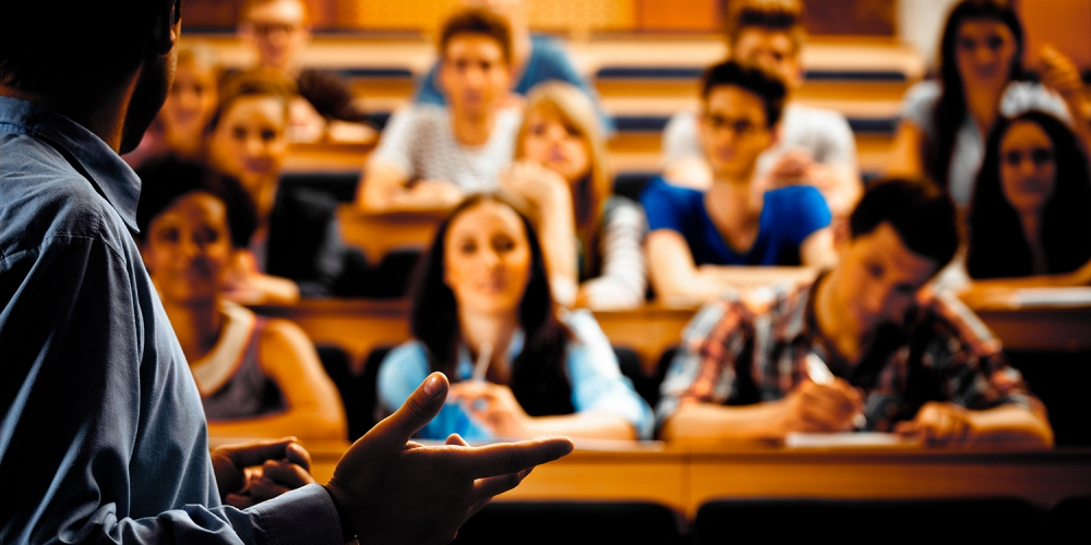Lecturer stands in front of a college seminar