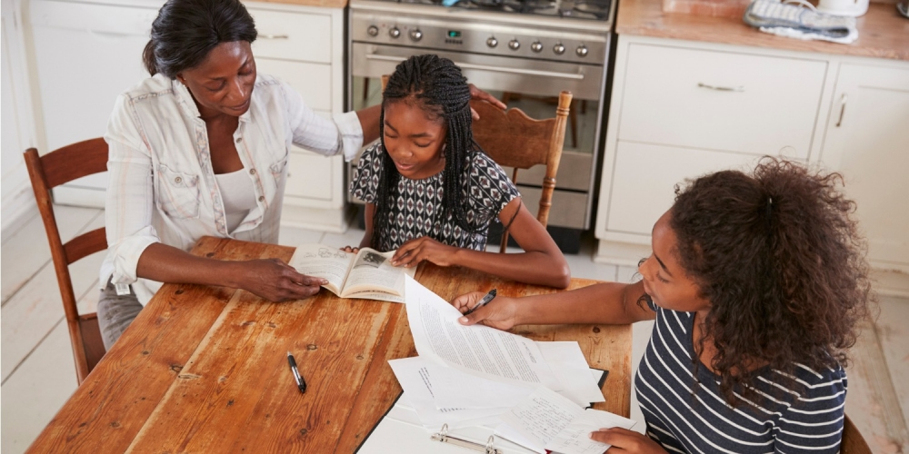 mother and two daughters doing homework at kitchen table