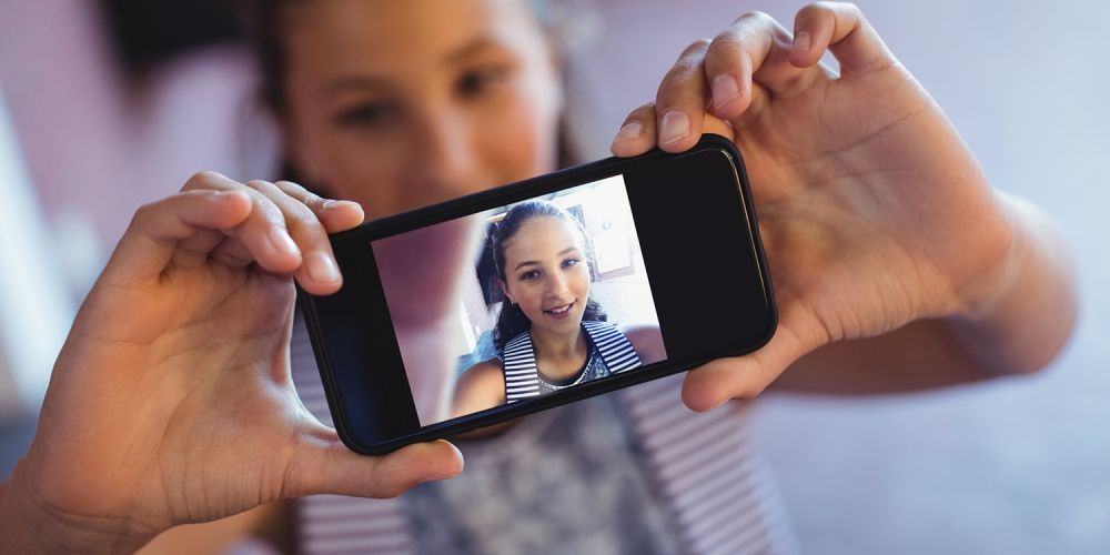 A photo of a teen holding up a phone with a picture of herself