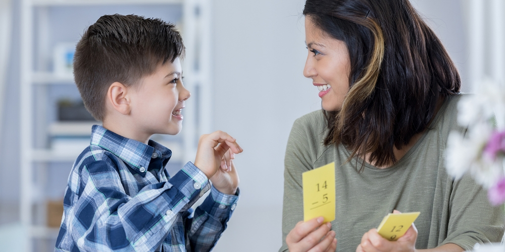 young boy and mother smiling at each other, with math flashcards