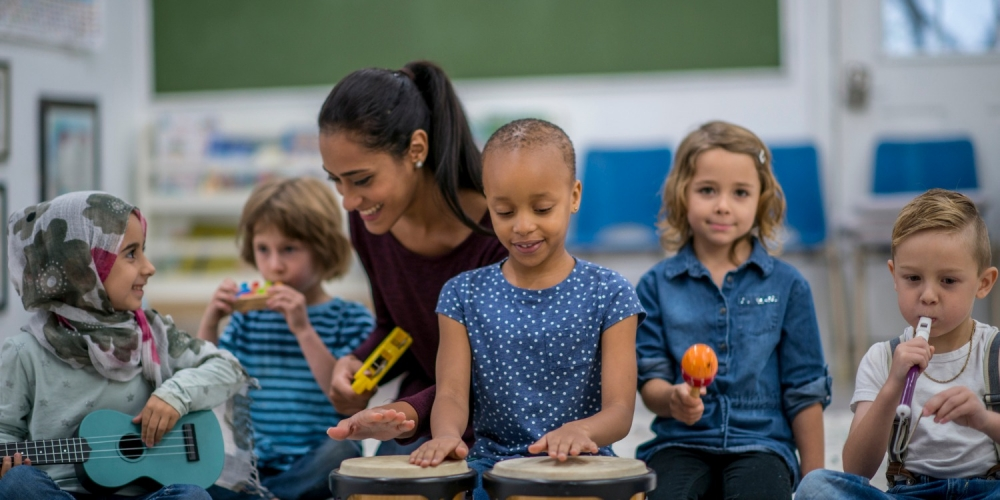 a diverse group of young students playing musical instruments with a teacher