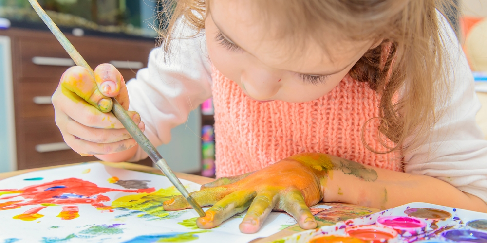 preschool-age girl using watercolors to paint outline of her hand