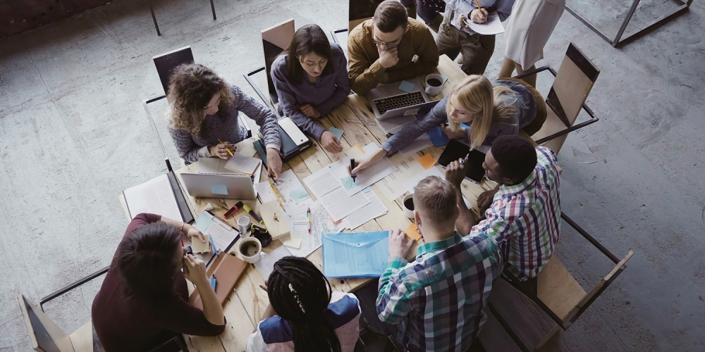 a group of college students, seen from above, working together around a table