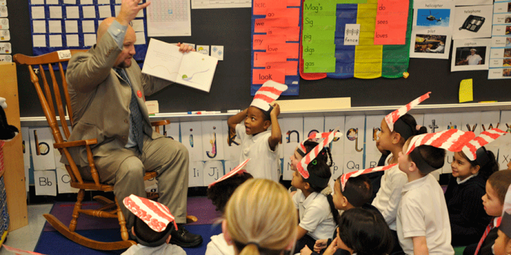 Lawrence receiver Jeff Riley reads to a group of students in Lawrence, Mass.