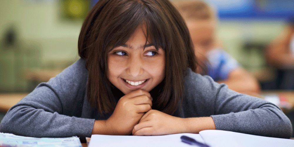 A photo of a female student smiling in class