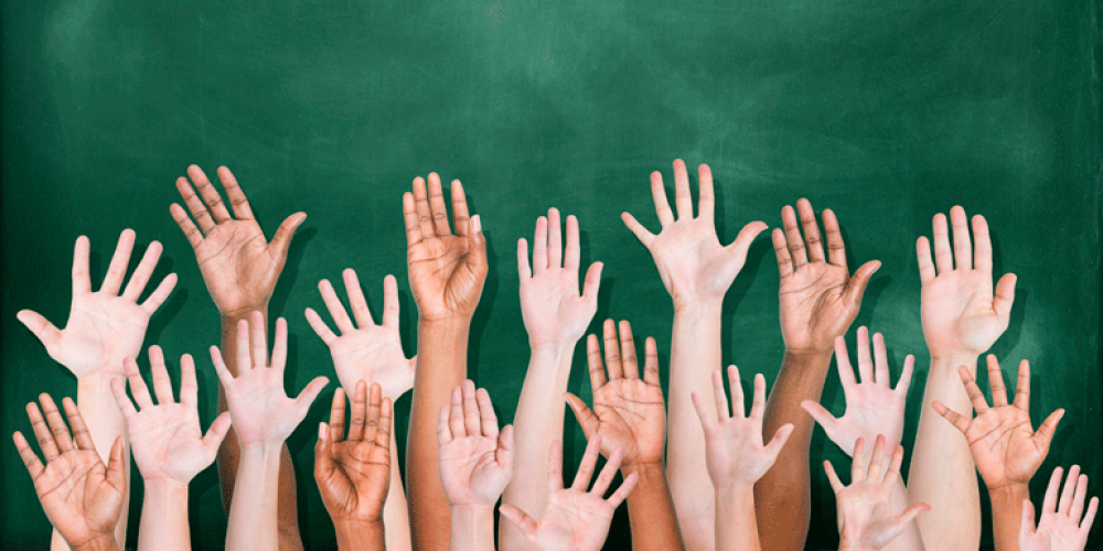 children's hands raised in front of a classroom chaulkboard