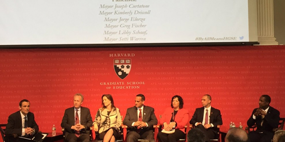 Six city mayors shown on stage at the Harvard Graduate School of Education