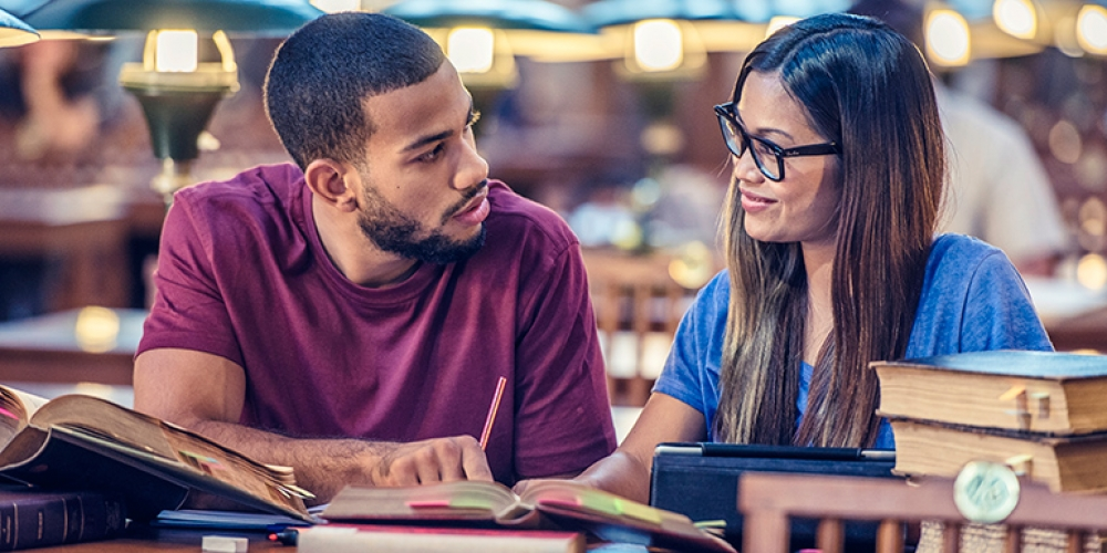 Male and female college student studying in library