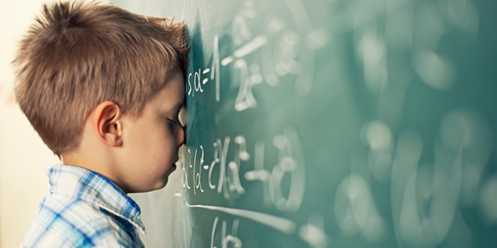 boy resting head on number-covered blackboard