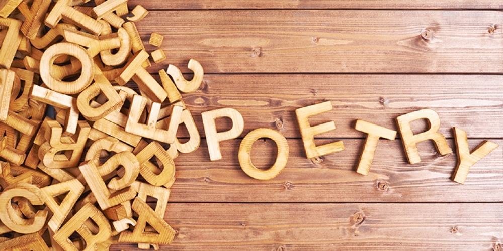 "jumble of wooden letter coming together to spell ""poetry"""