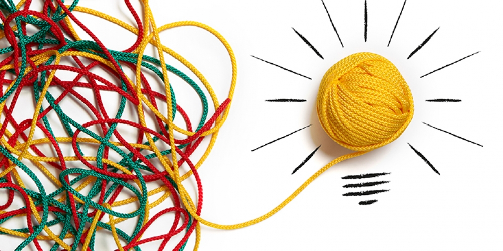 Messy strands of yarn coming together to form lightbulb