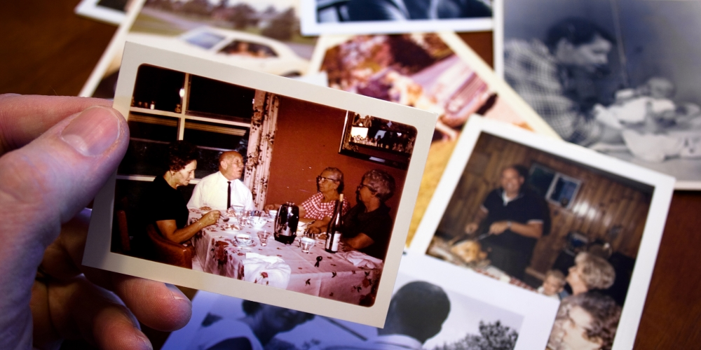 A photo of a hand holding old pictures of a family