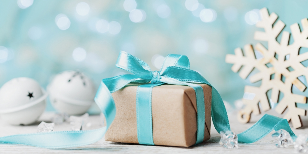 Picture of a brown wrapped gift and snowflake against a blue background