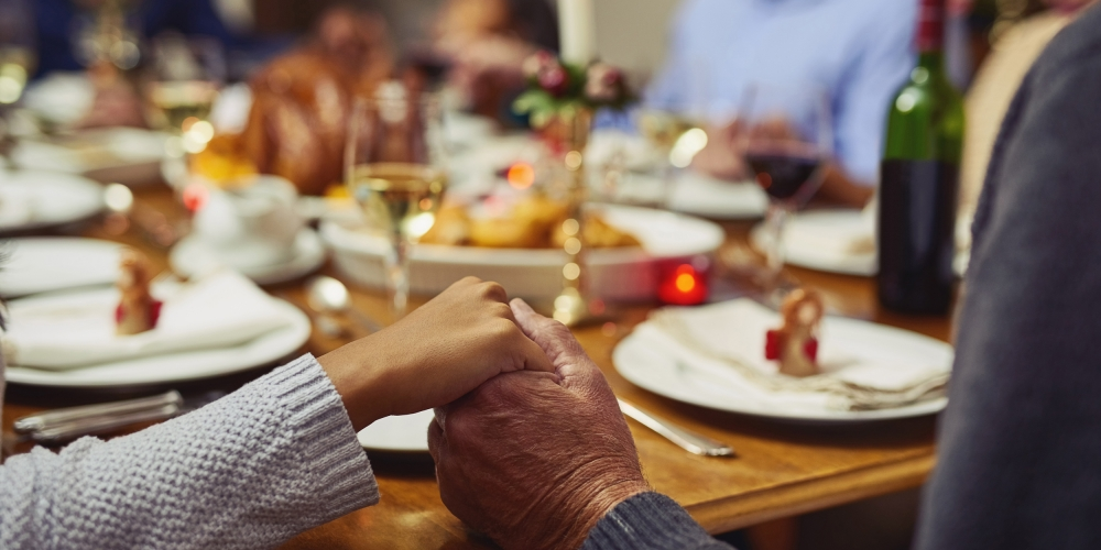 Photo of two people holding hands in front of a Thanksgiving table