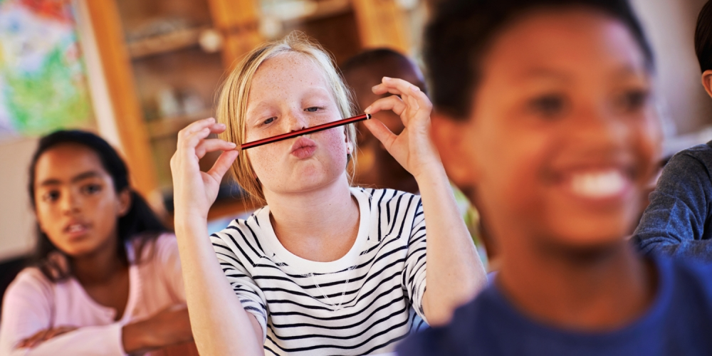 Photo of a girl goofing around with her pencil in class