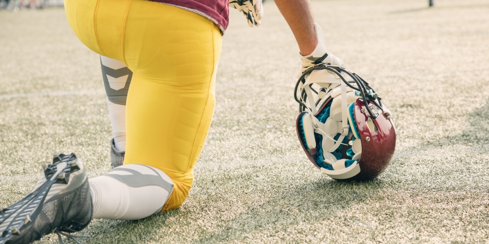 A photo of a football player kneeling next to his helmet